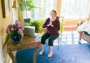 woman doing chair yoga with hands in namaste prayer