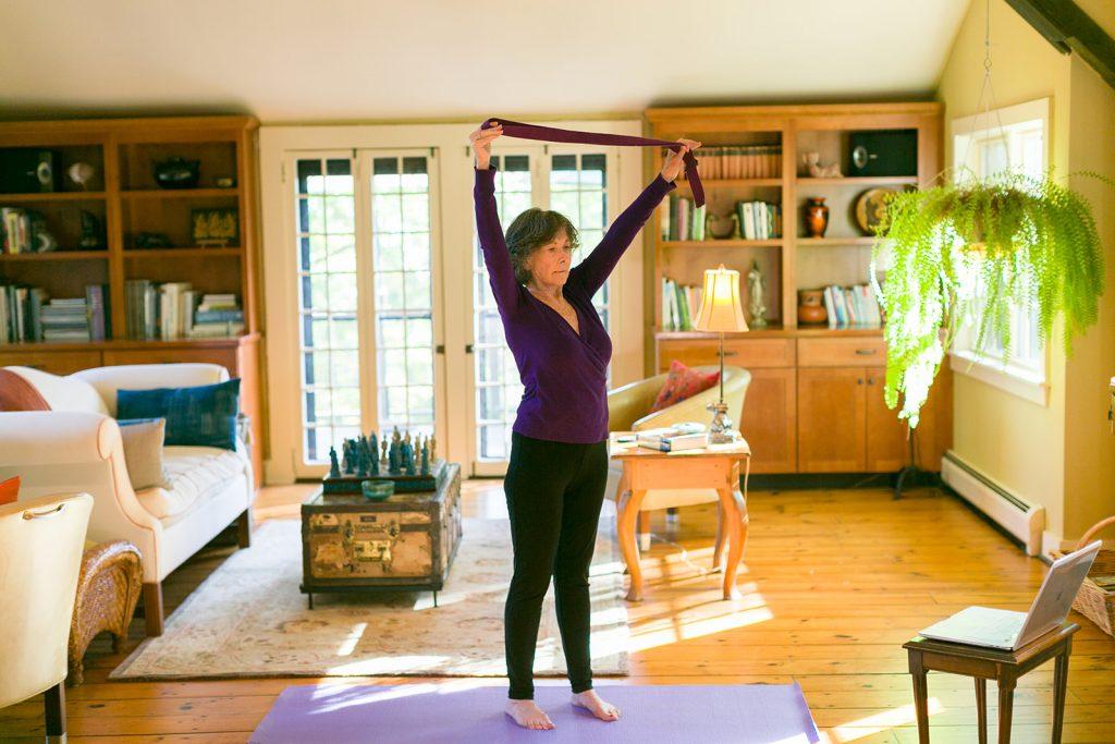 woman doing gentle yoga using a yoga strap