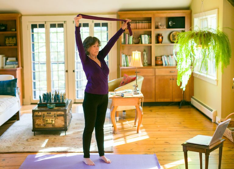 woman doing gentle yoga with yoga strap