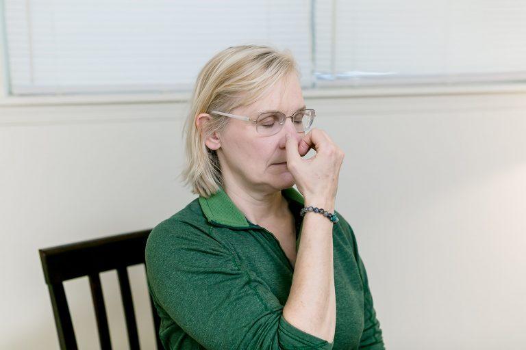 woman practicing alternate nostril yogic breathing called nadi shodhana
