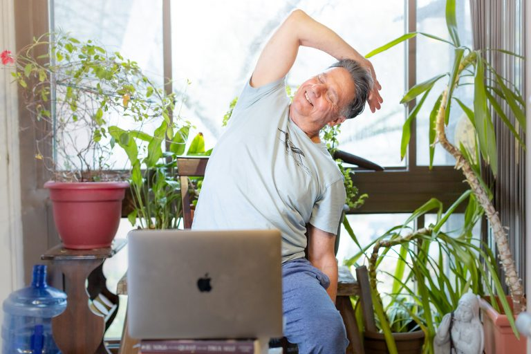 man doing side bend in online yoga class