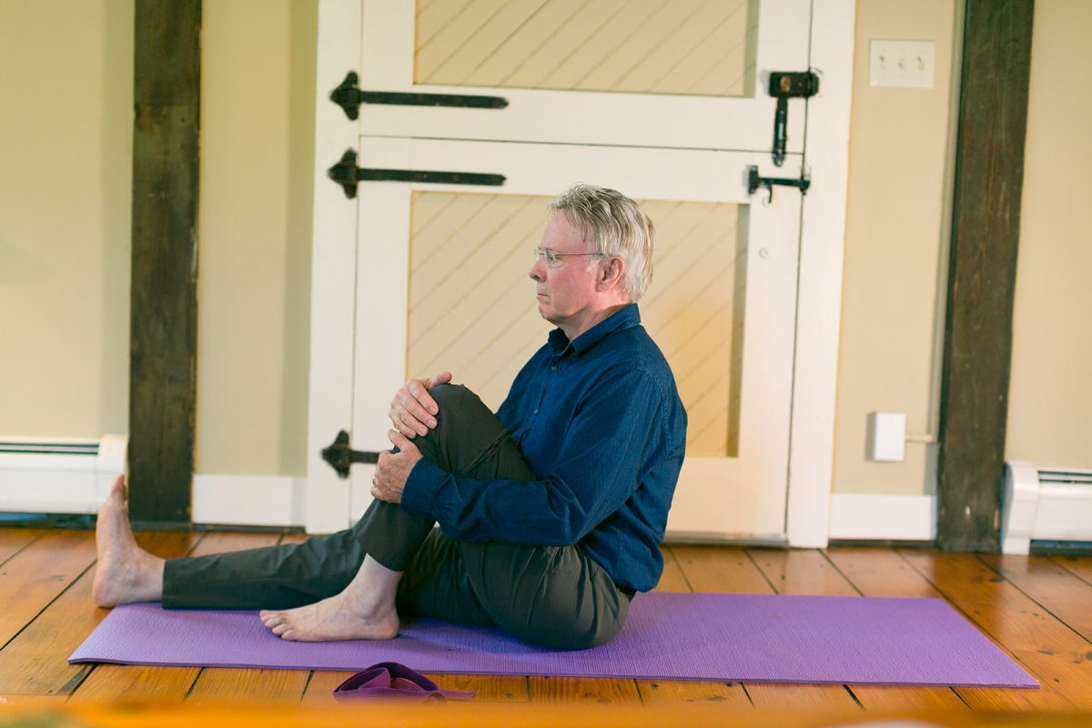 man on yoga mat preparing to do gentle yoga seated twist