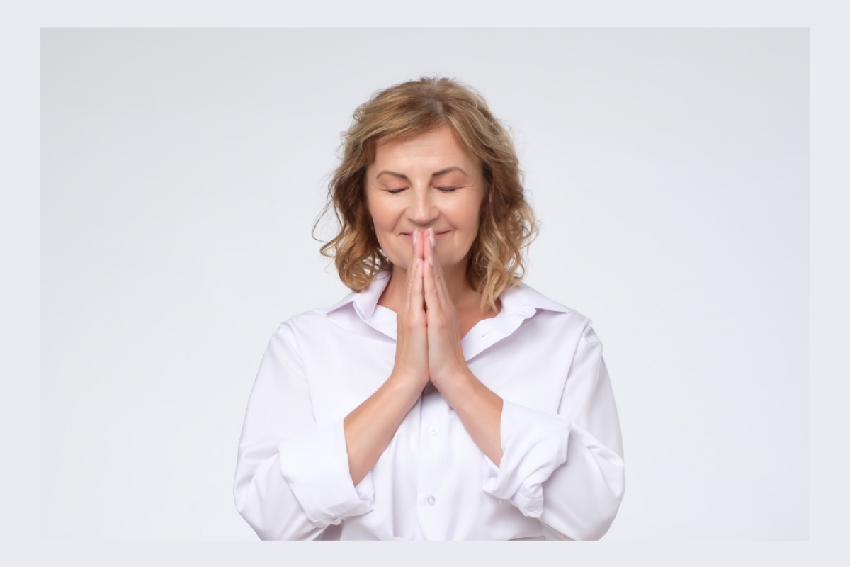 Woman with hands in prayer position feeling content